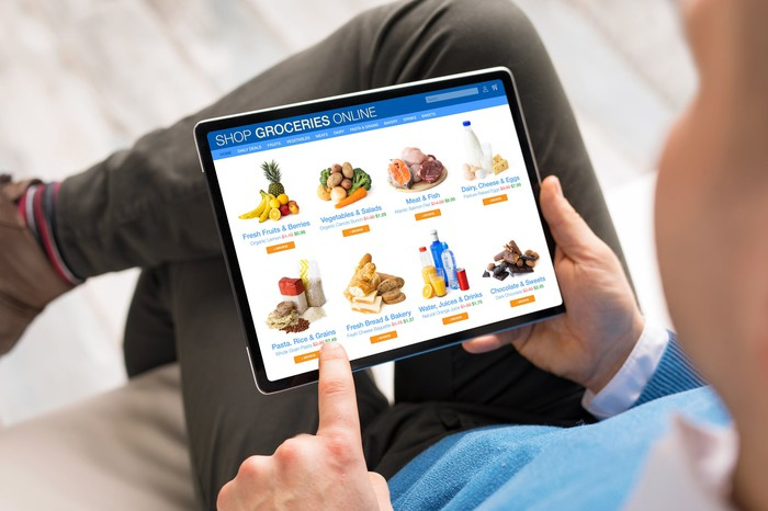 closeup on tablet with groceries on it as man shops for groceries.