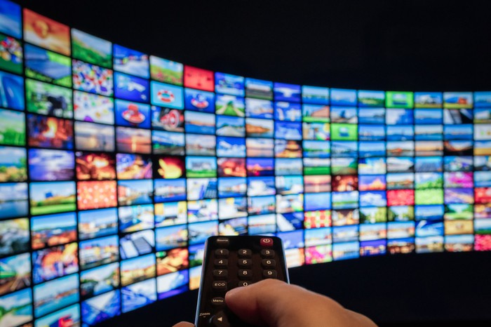 A hand points a TV remote at a wall with dozens of TV screens showing different images.