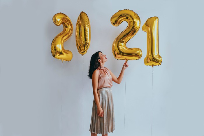 A woman looks at number balloons spelling out 2021