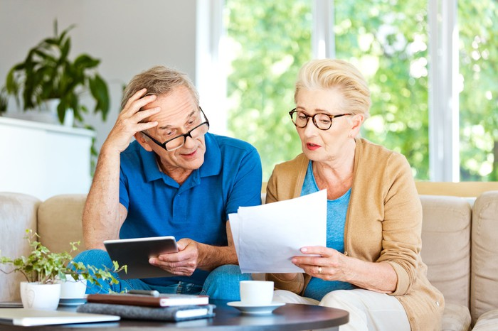 Older man and woman on couch looking at documents with worried expressions