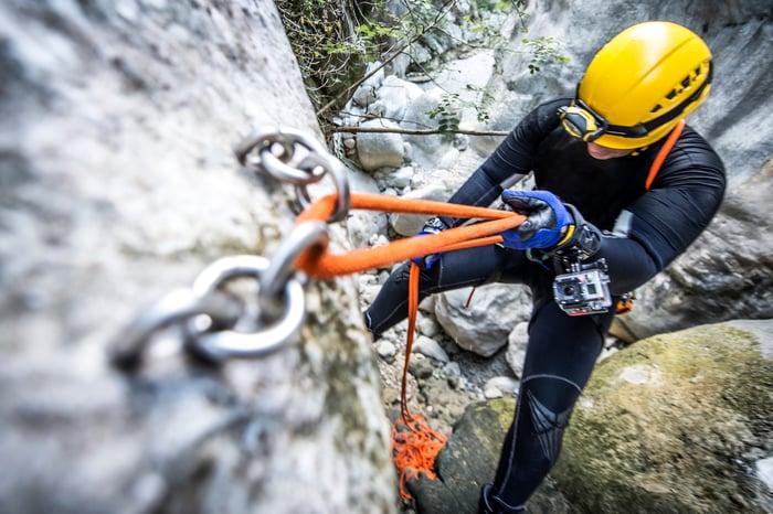 A rock climber descends  a steep rockface wearing an action camera on their wrist