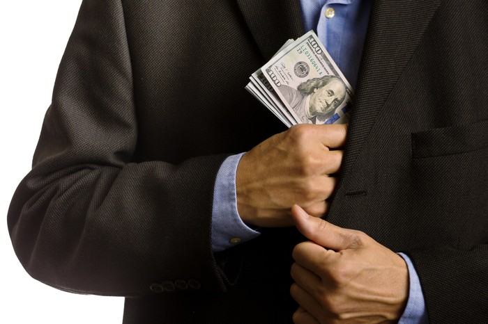 A businessman puts a thick stack of hundred-dollar bills in his jacket's inside pocket.