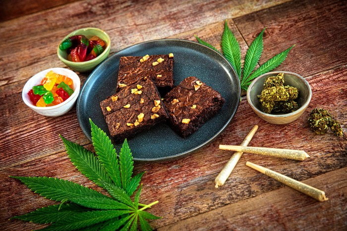 Marijuana leaves, joints, flower, and edibles on a wood table