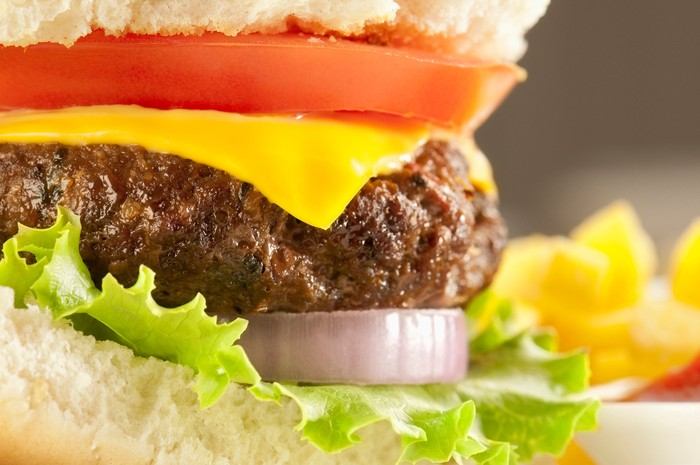 Close-up of a cheeseburger with lettuce and tomato