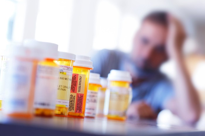 A man in the background struggling with addiction staring at bottles of opioids in the foreground.