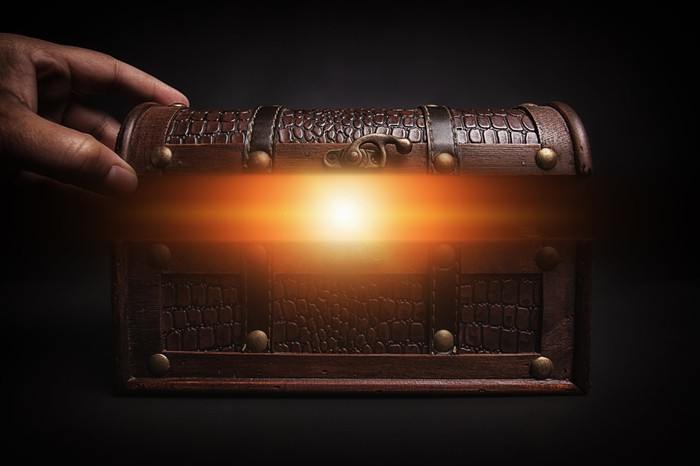 A hand starts to open a miniature treasure chest, revealing a glowing interior.