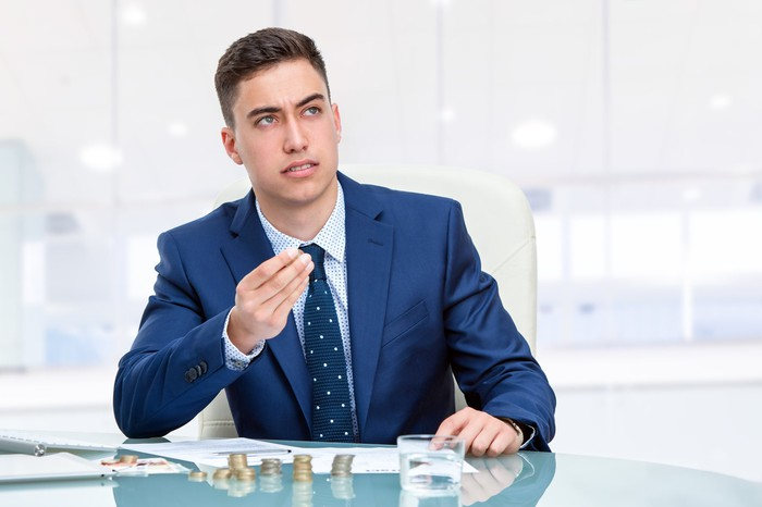Young businessman in blue suit sitting at desk in office with coin stacks on the desk.