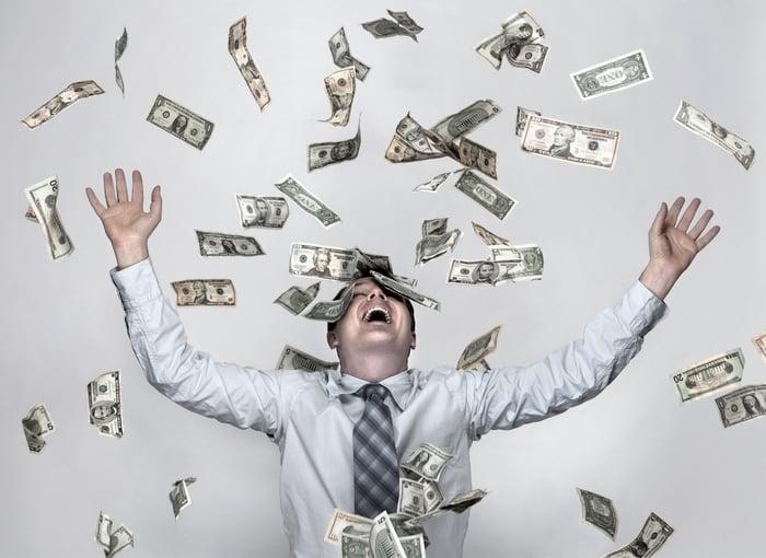 Smiling man raising arms while bills float around him