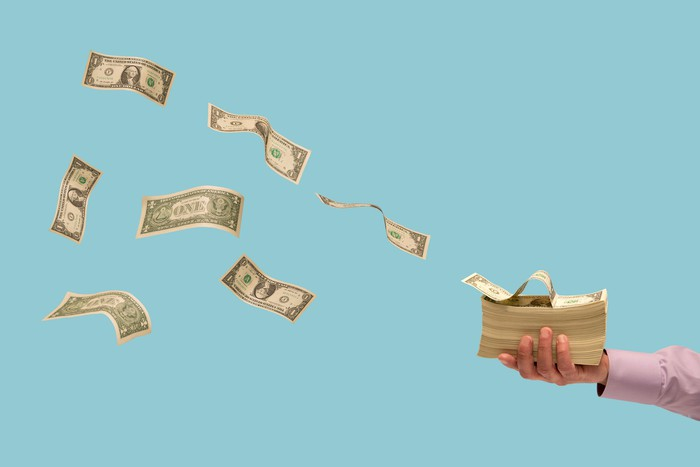 Stack of dollar bills against a blue background
