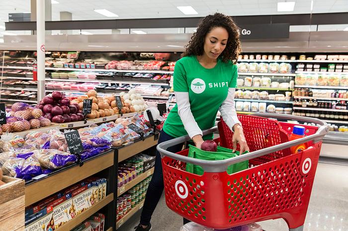 Une femme portant une chemise verte Shipt plaçant un article dans un panier d'épicerie cible