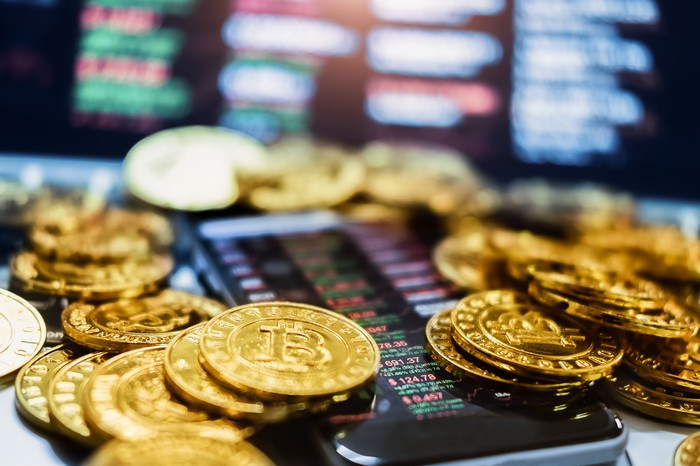 A handful of physical gold Bitcoin lying atop a smartphone that's displaying crypto price quotes and charts.