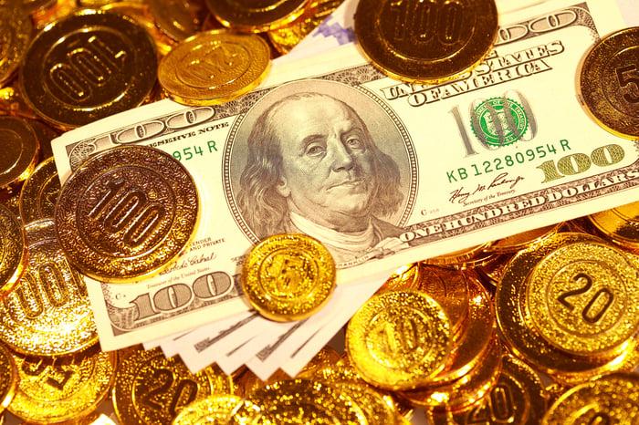 Gold coins strewn around dollar notes.