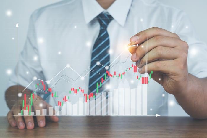 A businessman creates a digital financial chart.