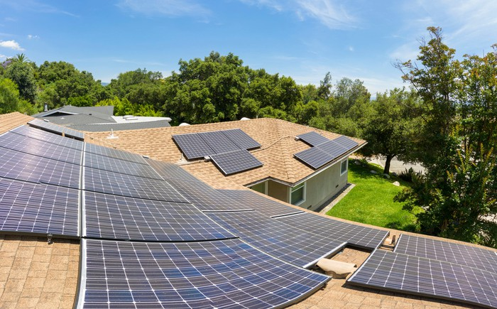Solar panels on a residential roof on a sunny day seen from tp of roof looking down.