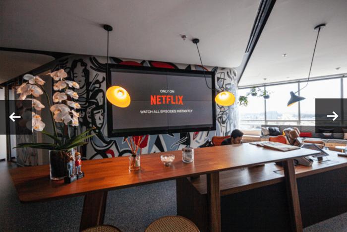 Netflix logo displayed on a large TV screen.