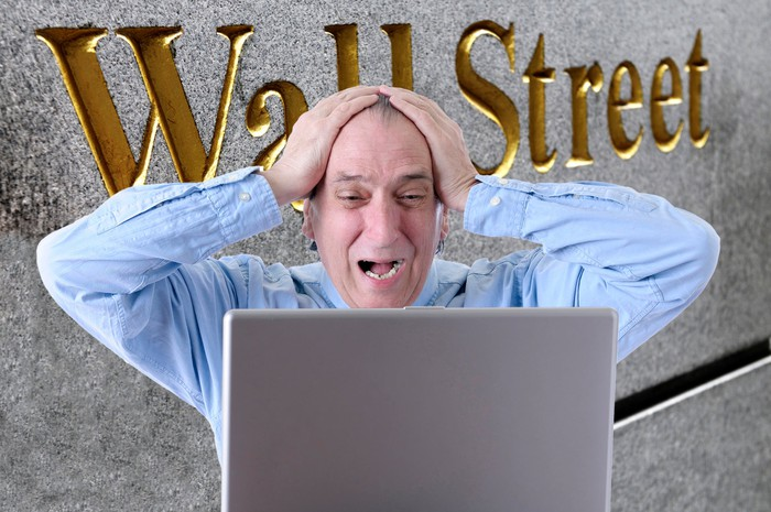 Man with hands on the top of his head and a worried expression looking at a laptop screen with the words Wall Street on a side of a building in the background.