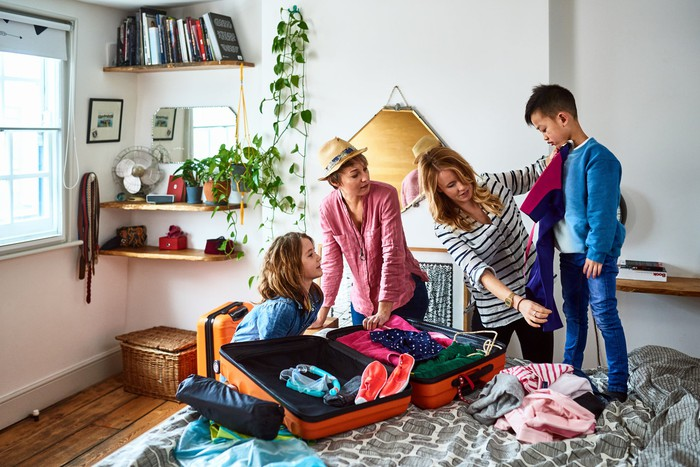 Two children and two adults unpacking a suitcase in a bedroom.