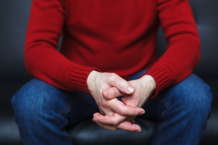 A man in a red sweater and blue jeans with is fingers crossed and his face not shown.