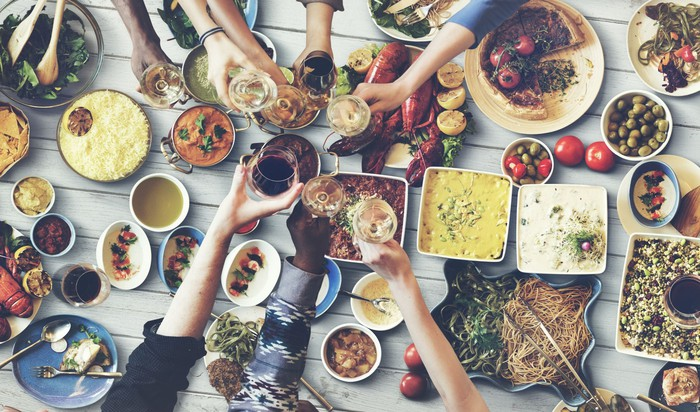 Six hands holding glasses outstretched above a table covered with many different dishes of food
