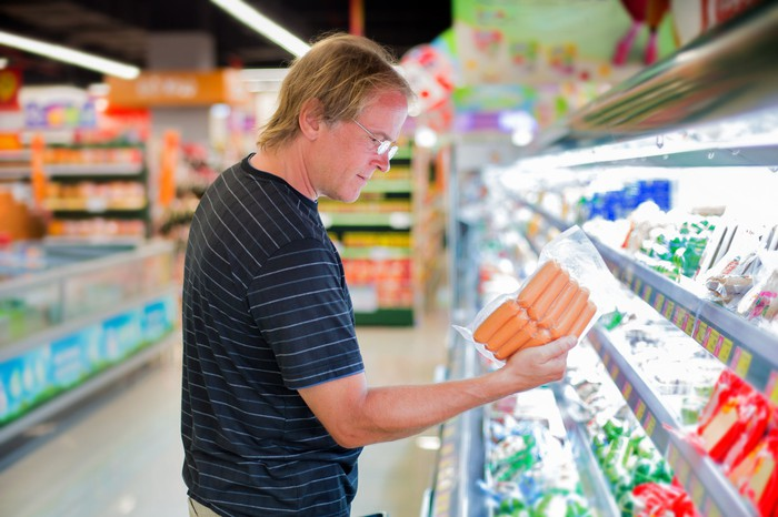 A man holding hot dogs in the supermarket aisle.