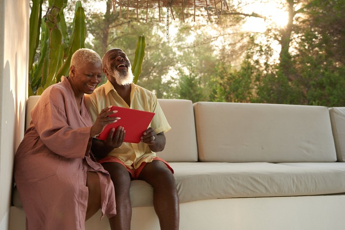 Older couple laugh with a digital tablet.