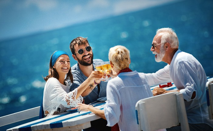 A group of four toasts with champagne on a cruise deck.
