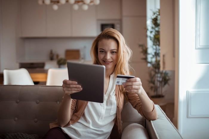 A young woman sits on her couch as she holds a tablet and a credit card.
