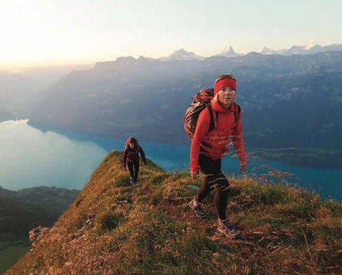 Two women hiking over mountain peak