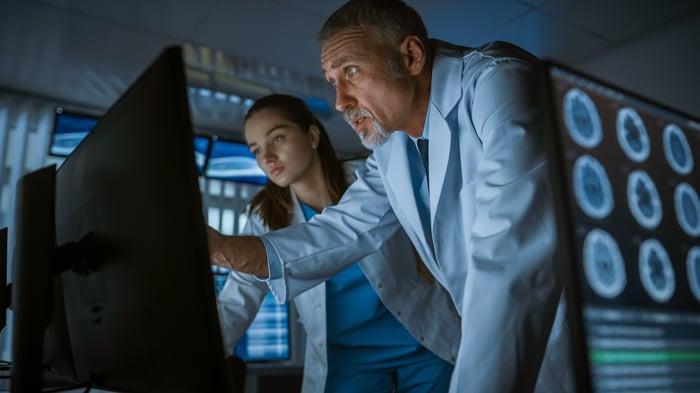 Deux neurologues consultent un ordinateur avec des lectures de scintigraphies cérébrales.
