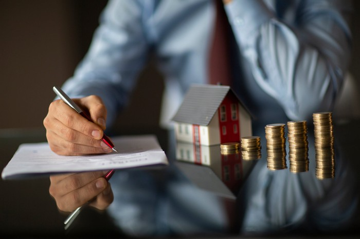 A landlord considers signing a paper on a desktop with a small house and several stacks of coins.