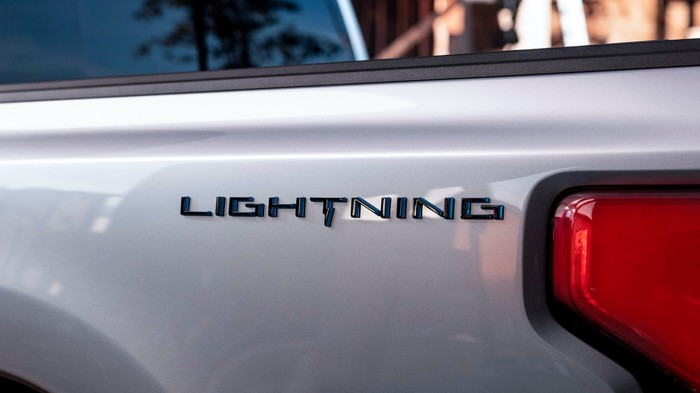 """A """"teaser"""" image showing the Lightning logo on a Ford pickup truck's flank."""