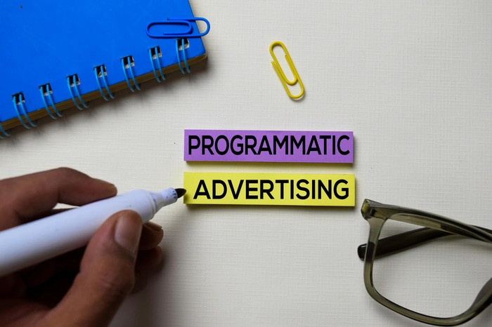 Notebook, paper clips, glasses, and pen in hand pointing to words Programmatic Advertising