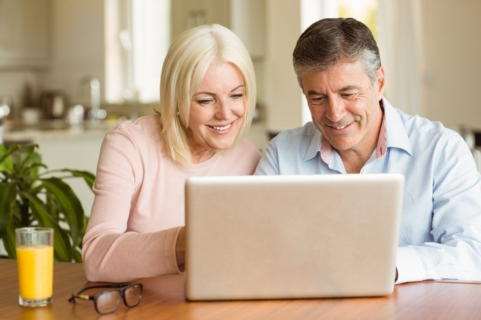 An older man and woman at a laptop, smiling.
