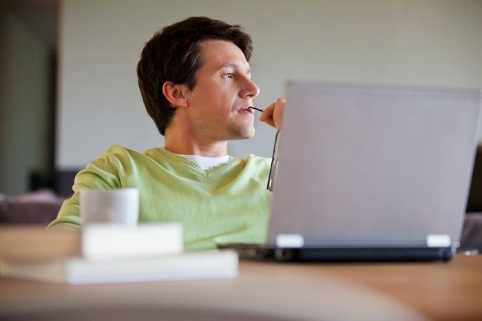 Man at laptop holding eyeglasses tip against mouth