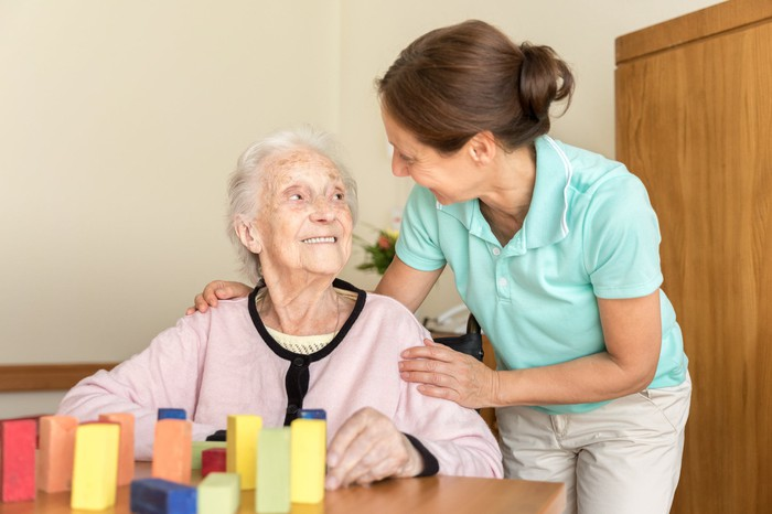An elderly woman doing a cognitive test with blocks being supported by a nurse.