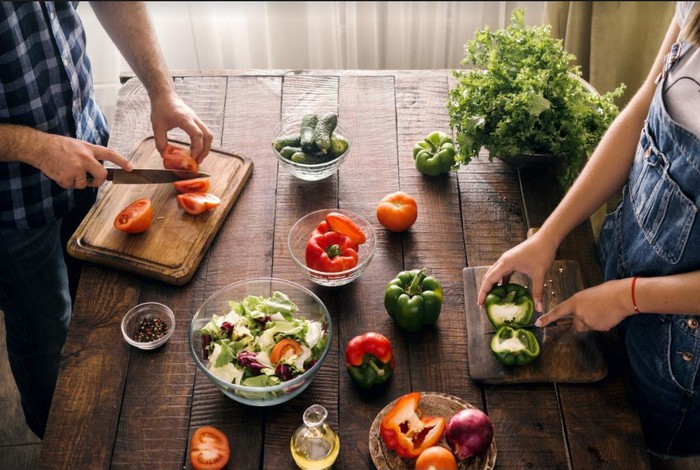 Two people chopping vegetables on a wooden counter.