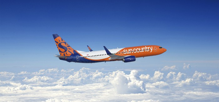 A Sun Country Airlines plane flying over clouds