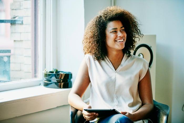 Heureuse jeune femme assise dans une chaise près de la fenêtre ensoleillée tenant la tablette
