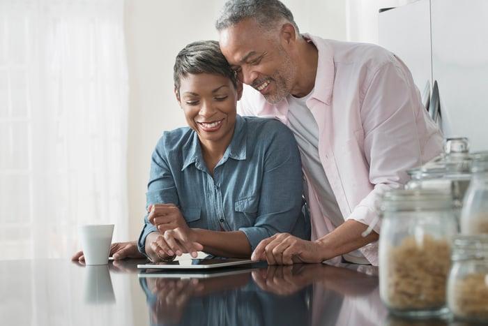 Couple souriant au comptoir de cuisine en examinant une tablette