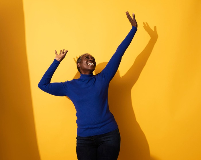 Happy person dancing against a bright yellow background.