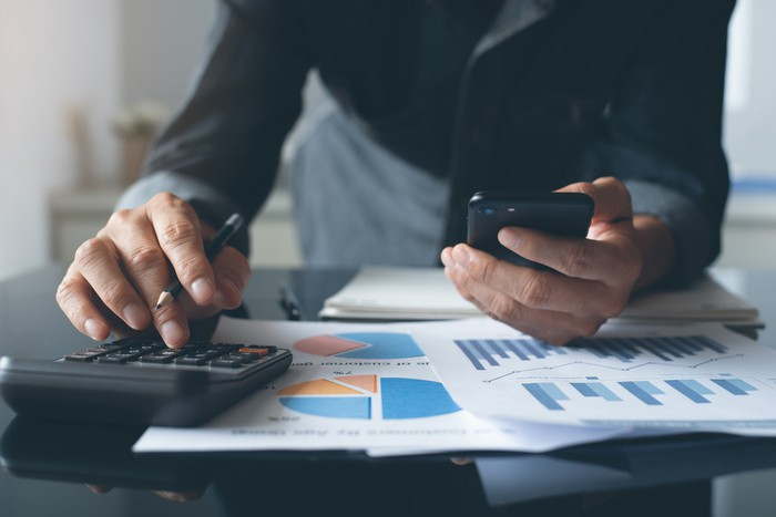 Holding a smartphone, a man works with financial charts and a calculator.