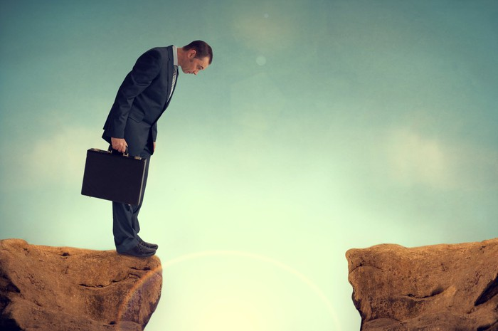 A businessman standing at the edge of a cliff looks down into the abyss.