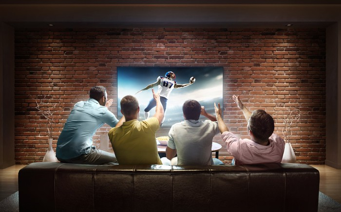 Four friends watching a football game on a wall-mounted TV.