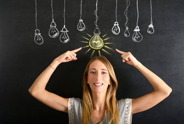A woman pointing to a lit chalk lightbulb above her head.