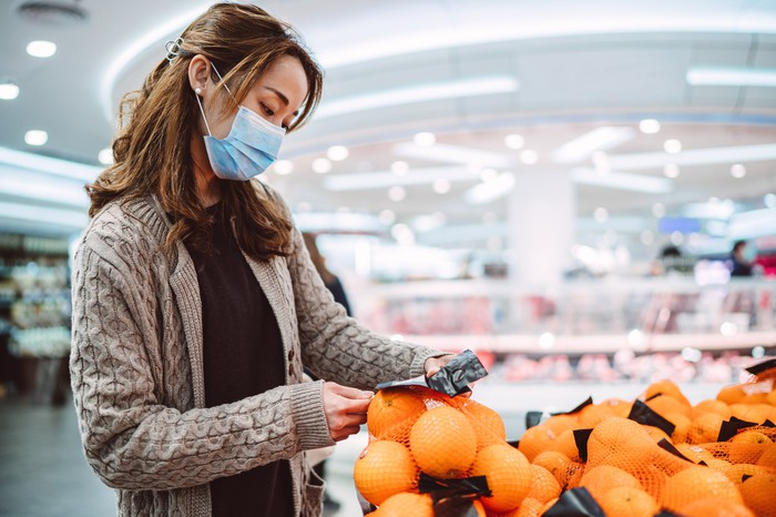 A woman wearing a mask picking oranges in a supermarket.