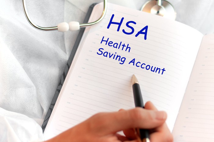 Doctor holding notebook that says health savings account with pen pointing to those words
