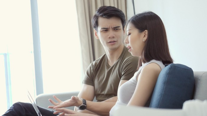 Couple talking while woman gestures to laptop screen