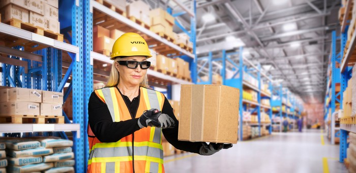 Woman in a warehouse waring Vuzix smart glasses and safety equipment