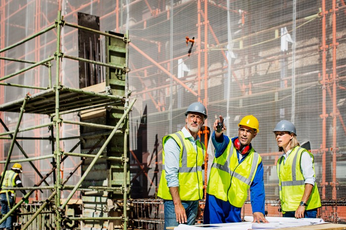 A group of workers in hard hats discussing a site plan at a construction site.