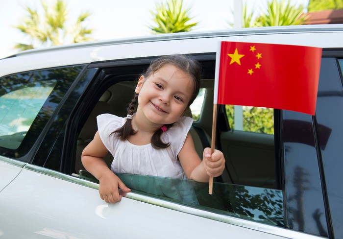 Little girl waving a Chinese flag out of a car window